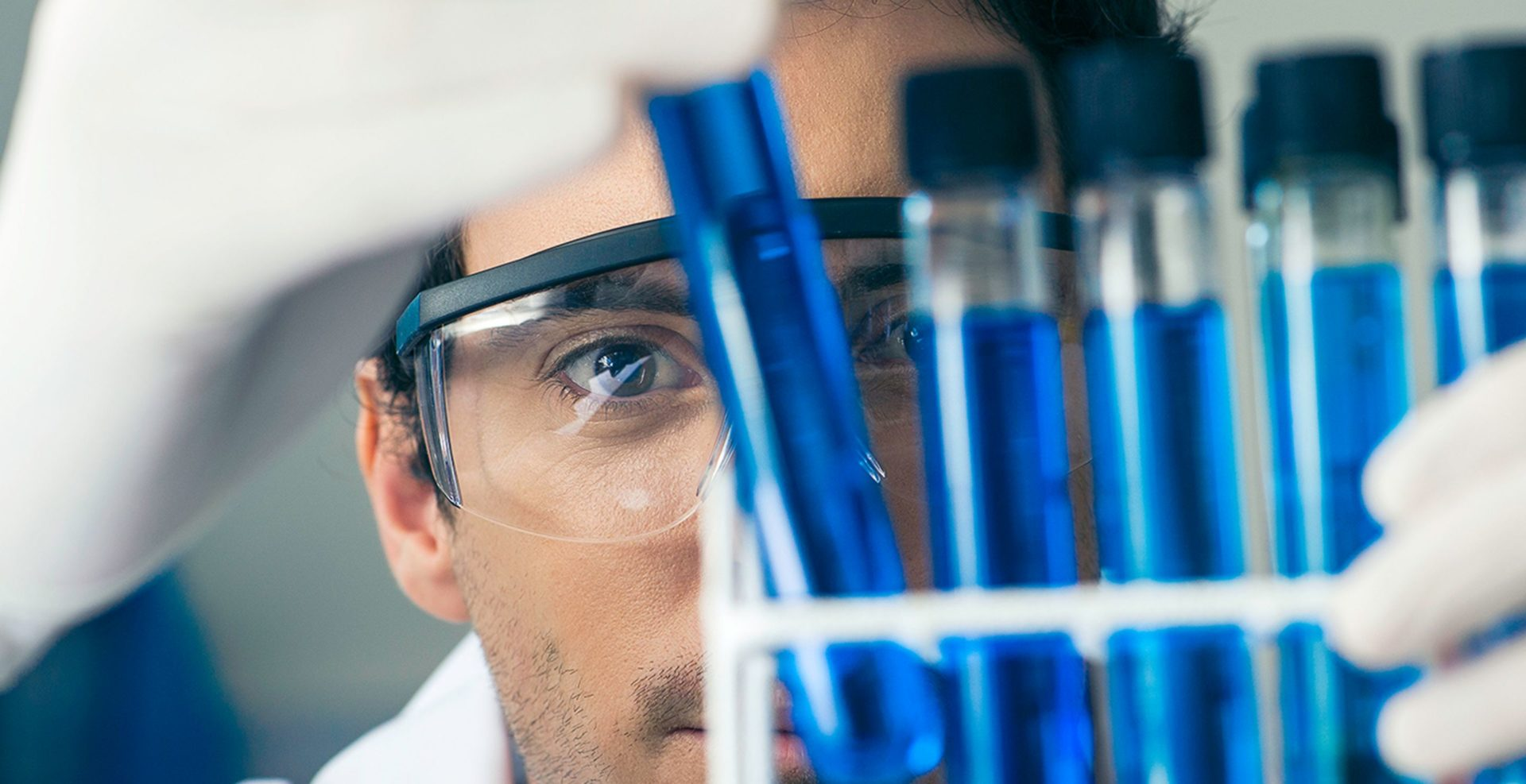 A man wearing goggles stares into a tray of test tubes.
